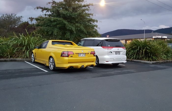 yellow holden ute and white family wagon